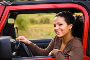 Portrait of a woman sitting in a car and smiling